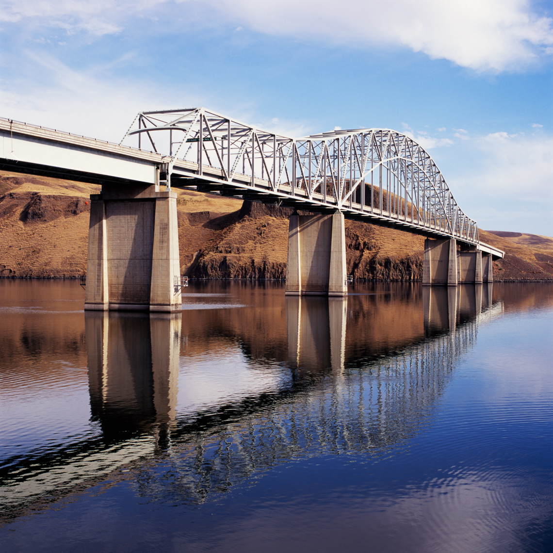 Steel and concrete highway bridge over river. Transportation engineering construction industry.