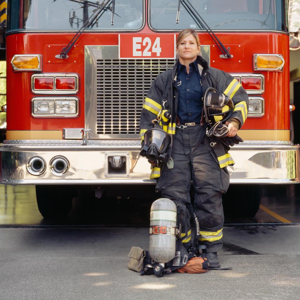 Female woman firefighter with technical gear and fire engine truck. Capable, confident, proud career professional.