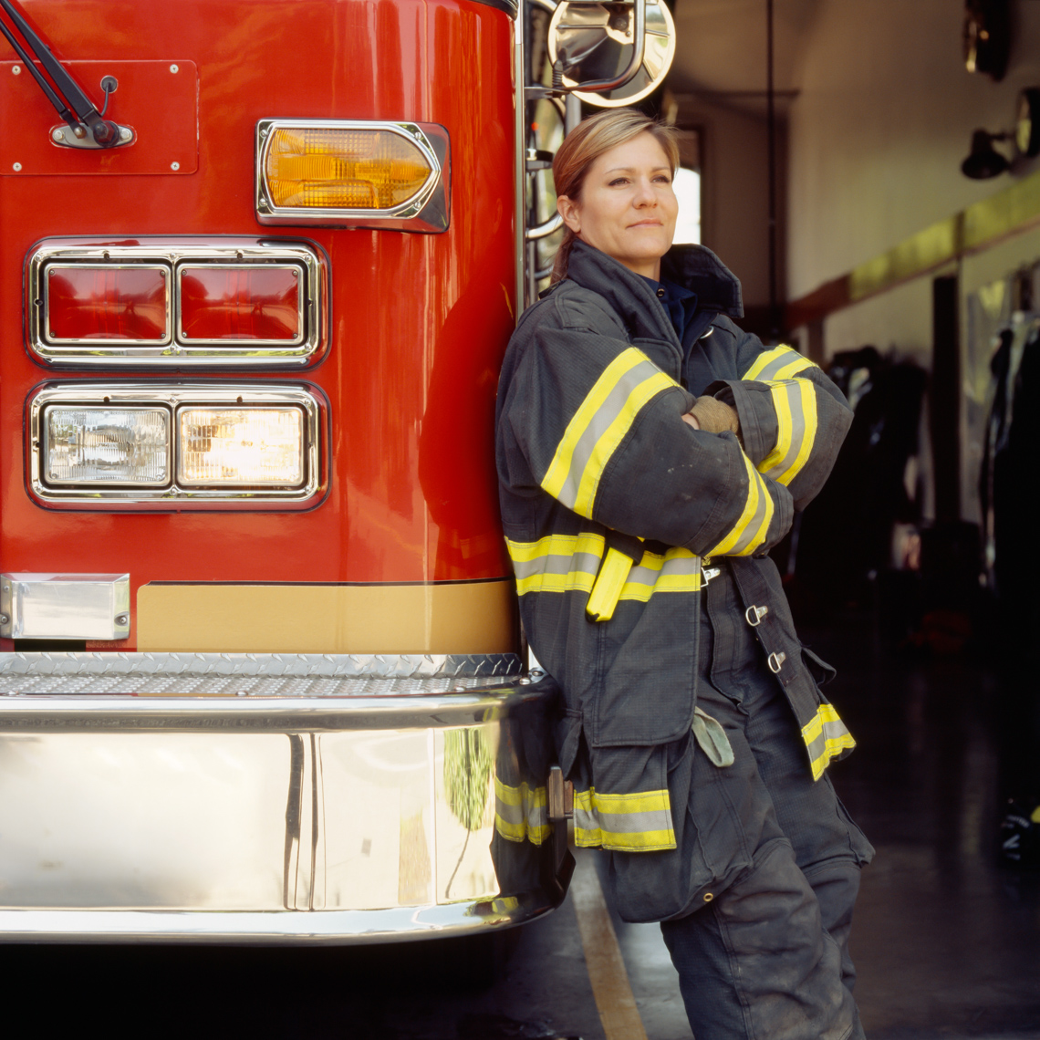 Smiling female woman firefighter wearing technical clothing bunker gear with fire engine truck at station. Confident, proud public service career professional.