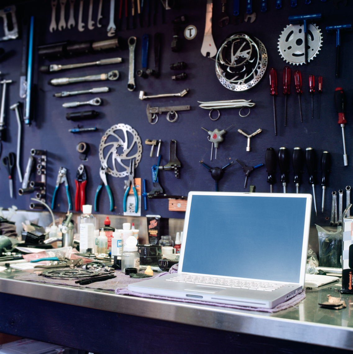 Laptop computer with blank monitor screen on workbench in bike shop. Small businesses staying organized using technology.