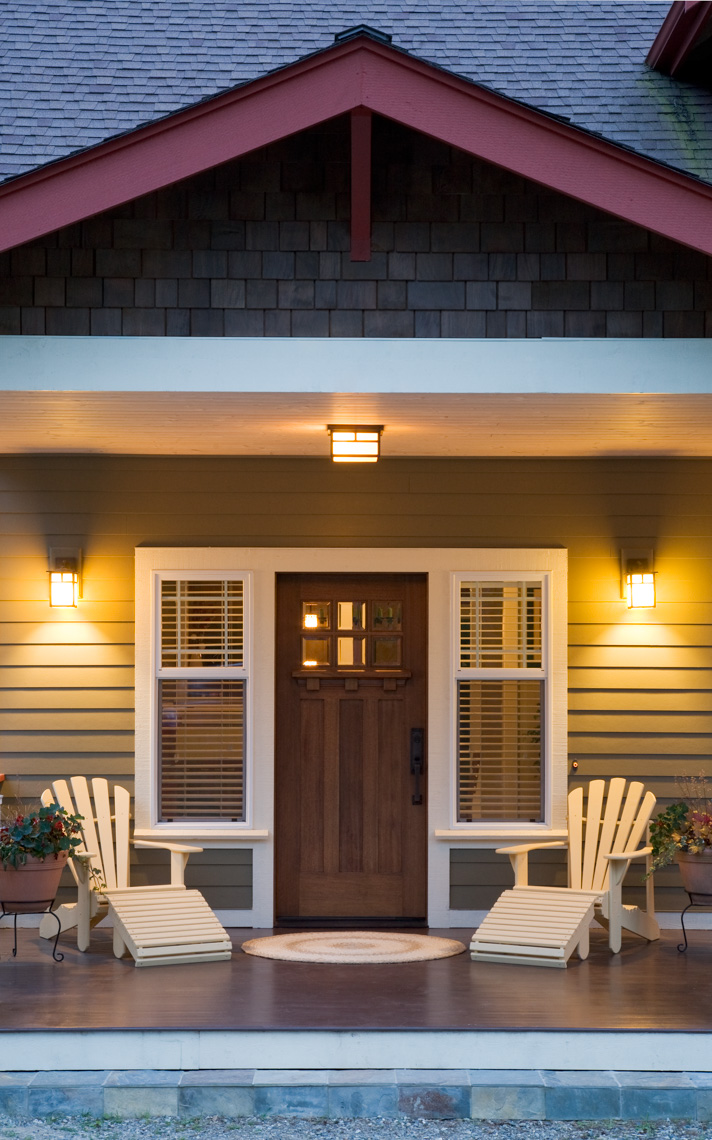 Front porch and entry of traditional Craftsman style home at  twiight dusk with windows, wooden front door, exterior lighting and Adirondack chairs