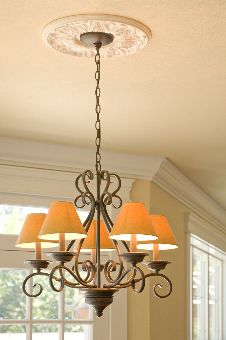 Chandelier hanging from ceiling in traditional home with windows in background