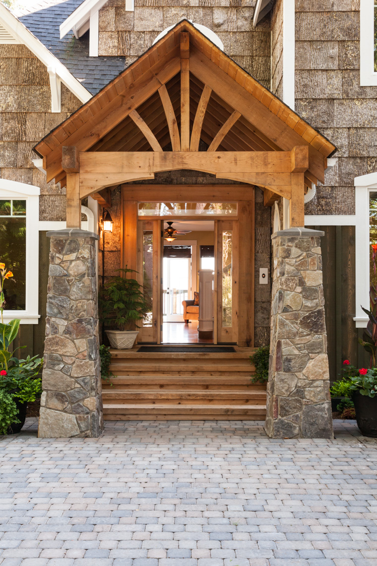 Stone and wood front porch entryway to upscale country house with open front door and paving stone driveway.