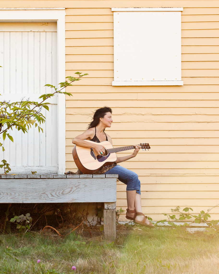 Beautiful, happy, healthy, creative young woman playing guitar outdoors. Women