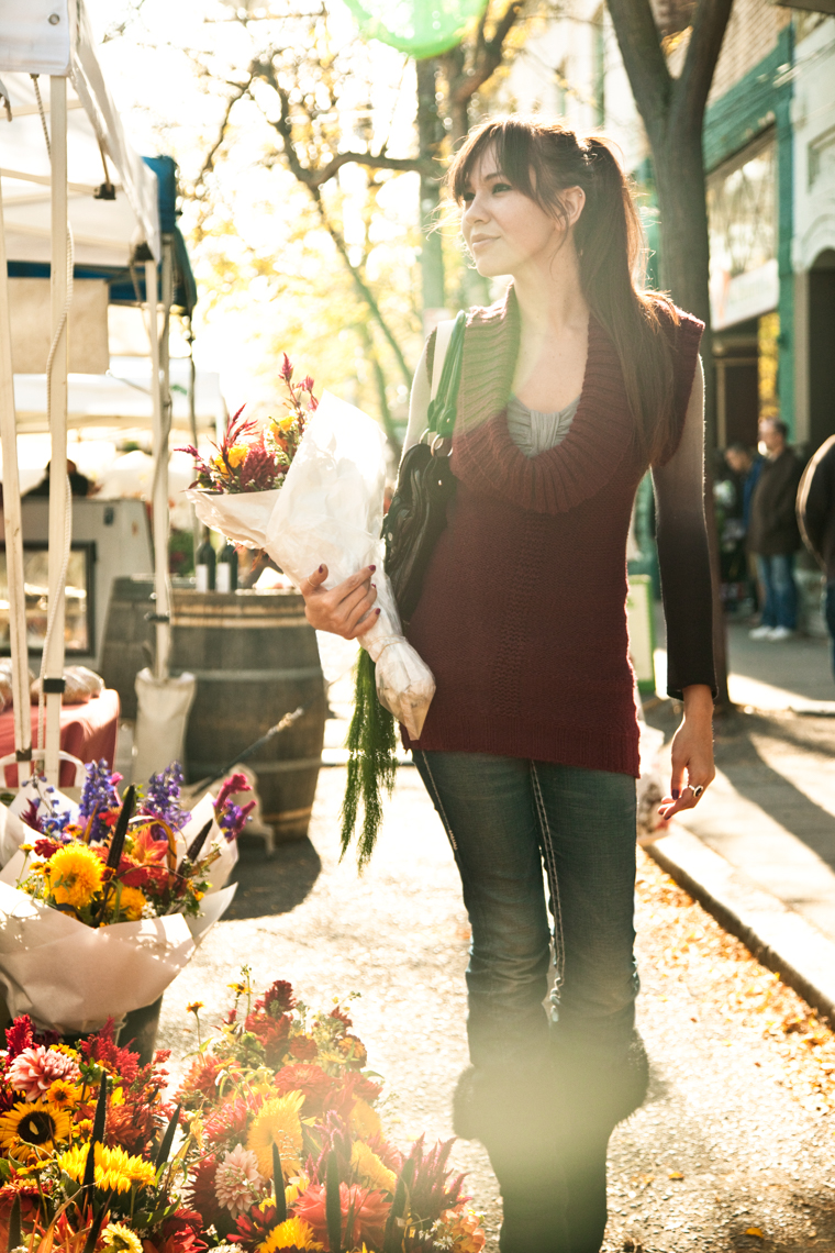 Young Hispanic woman with flowers walking at Farmers