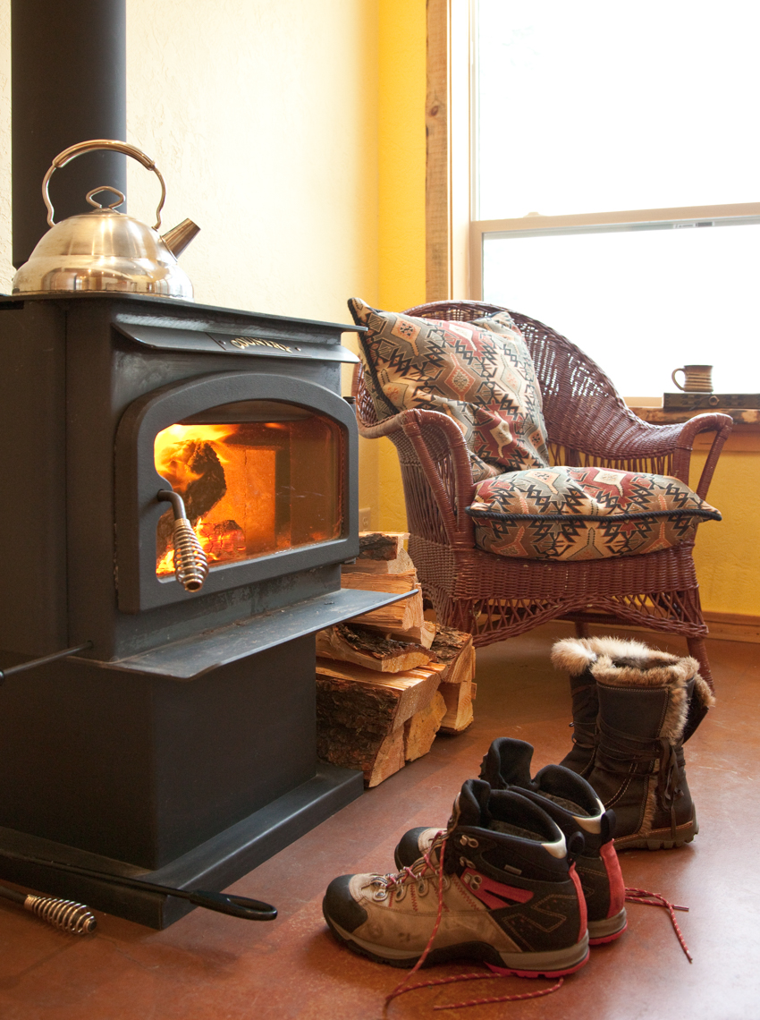 Cabin interior with wood burning stove, chair and boots. Winter vacation getaway.