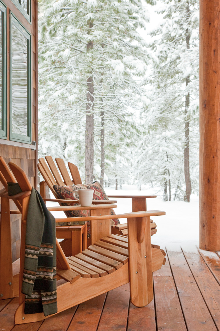 Adirondack chairs on deck with snowy landscape in background