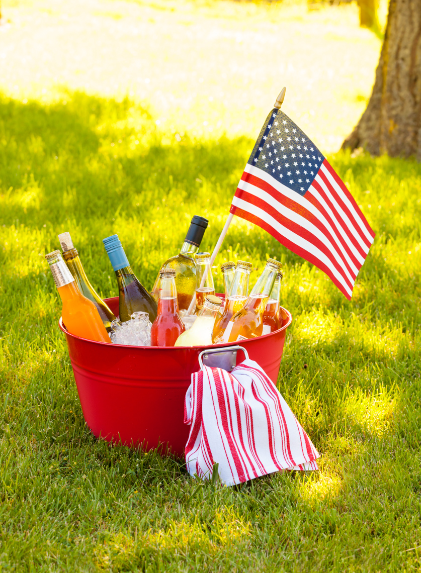 Cold drinks wine, beer and soda on ice in red bucket pail tub with American flag  on green grass. Summer outdoor backyard Fourth of July 4th garden party picnic.