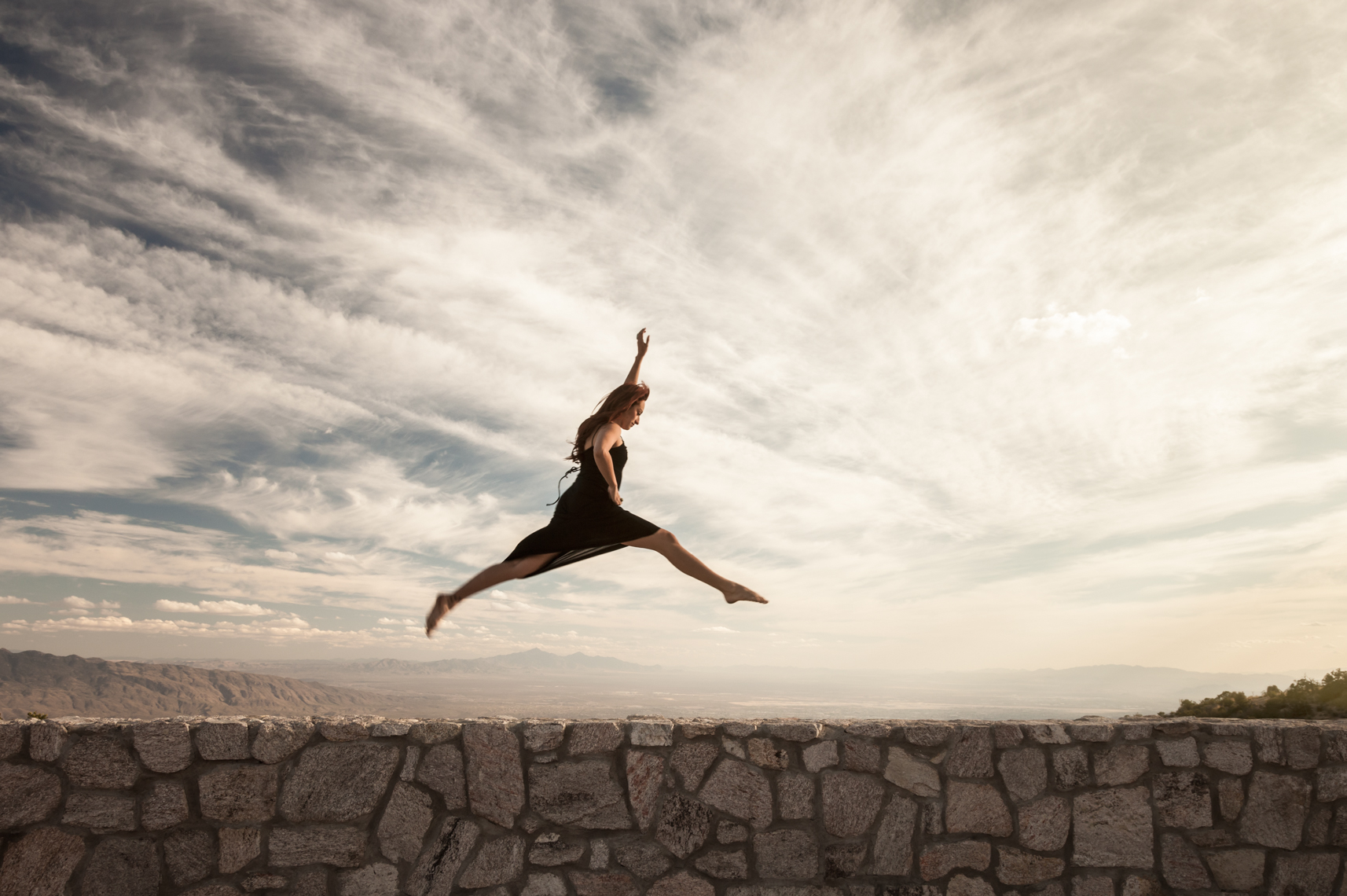Beautiful, healthy, strong, Hispanic woman leaping jumping over stone wall with dramatic sky background