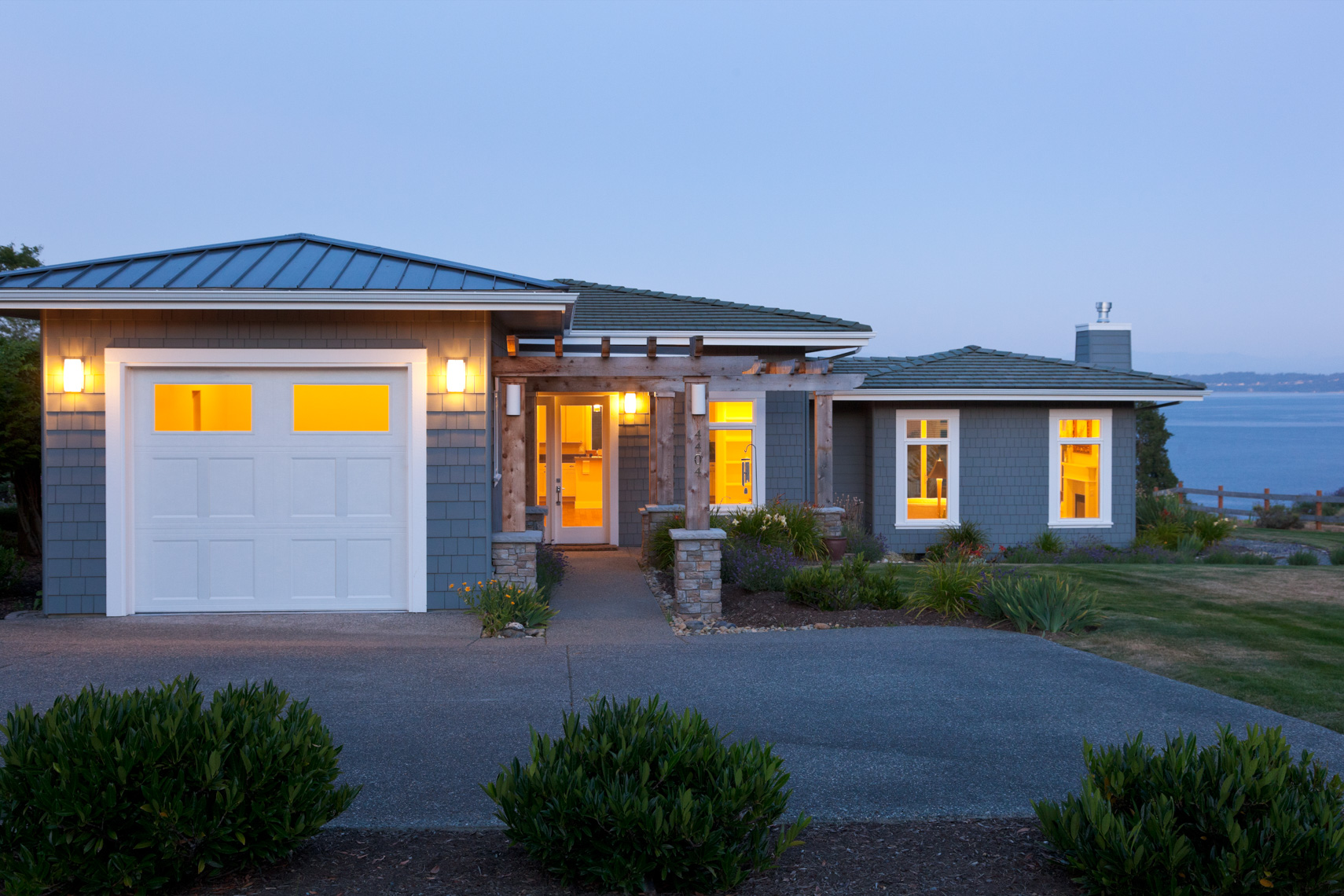 Contemporary house and garage at dusk with exterior lighting and lights on inside. Home energy use, water view real estate.