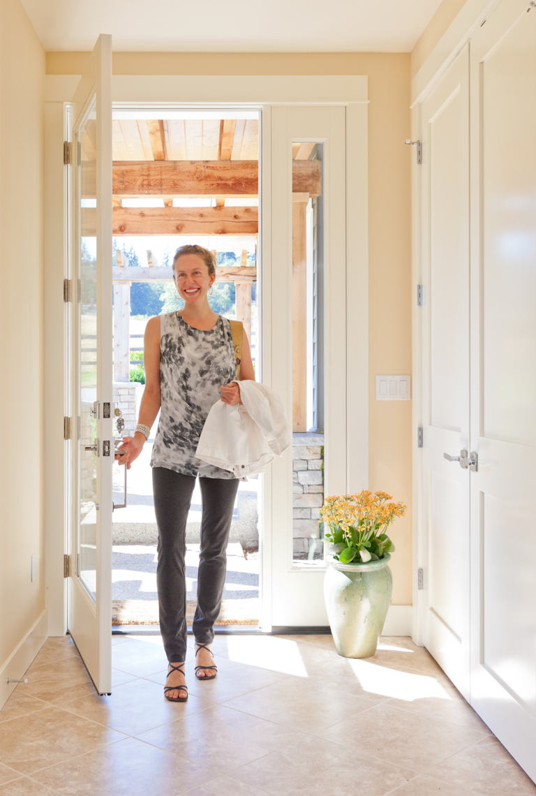 Happy smiling woman home owner homeowner opening front door entering coming home