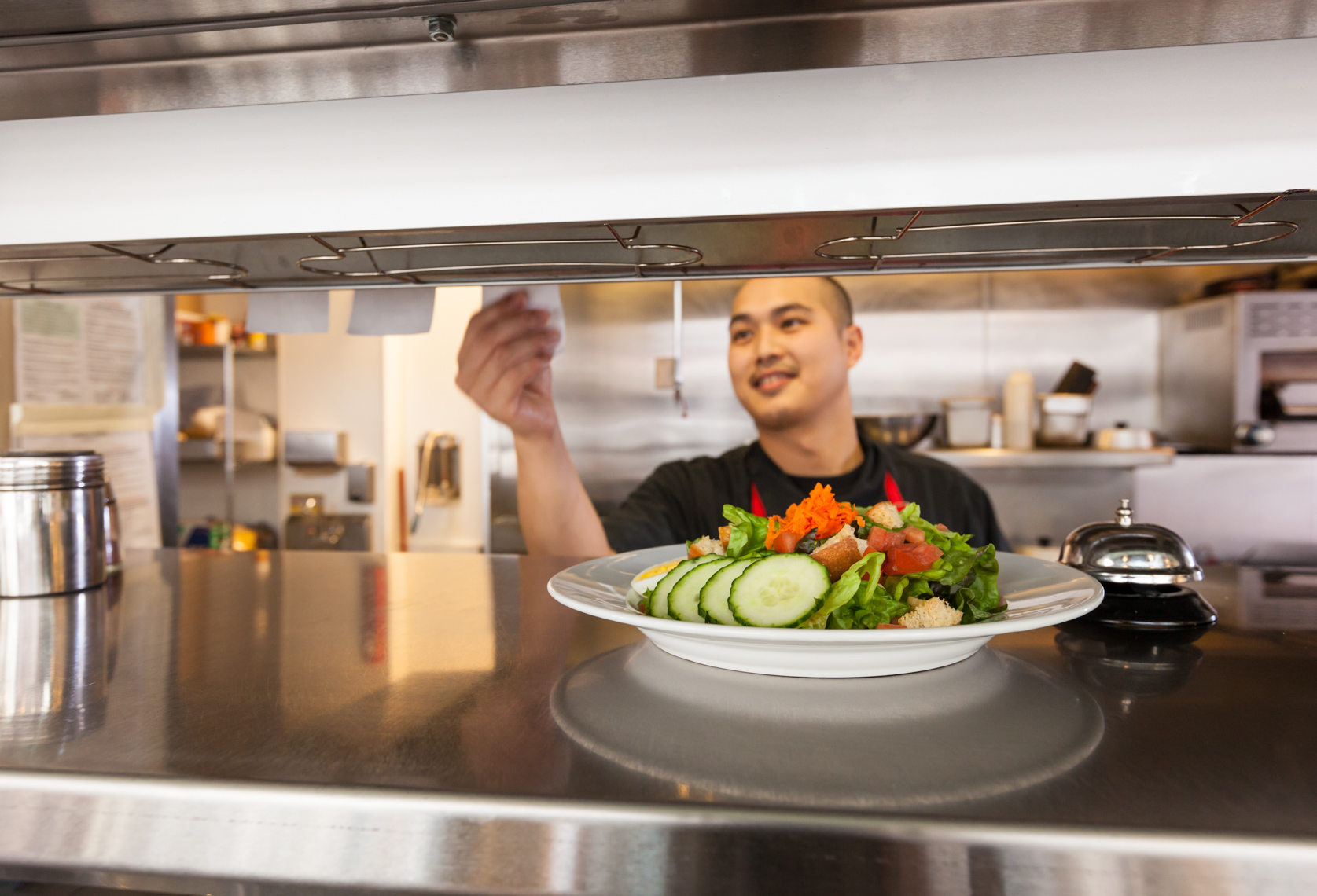 Happy young Asian man chef cooking working preparing food in restaurant kitchen