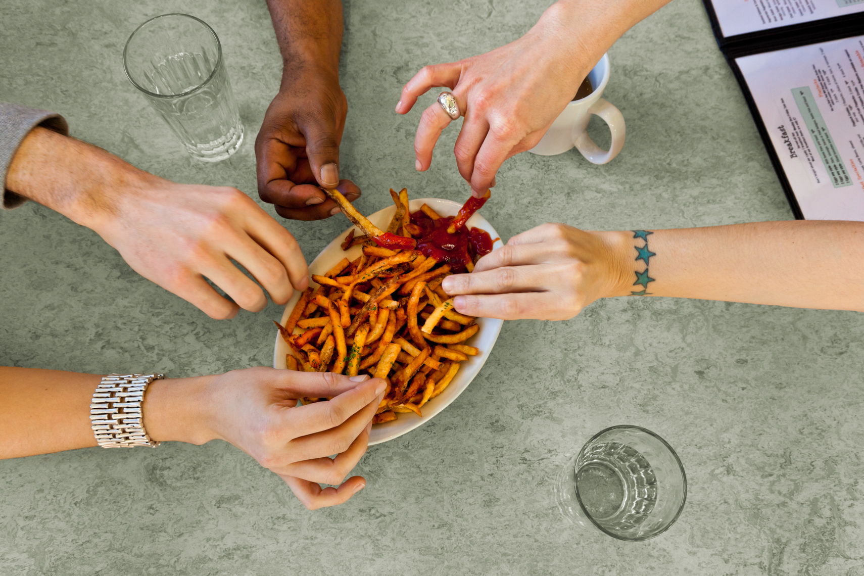 Hands of diverse group of friends eating sharing French fries food in casual restaurant
