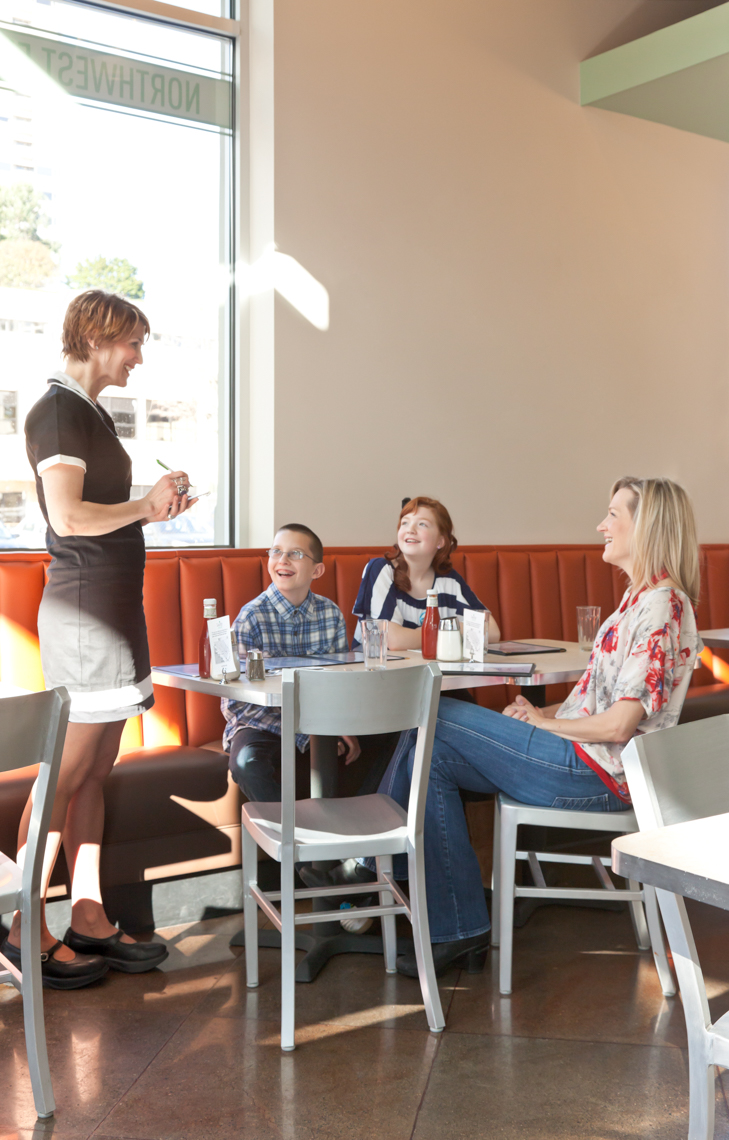 Waitress taking order from family in casual restaurant