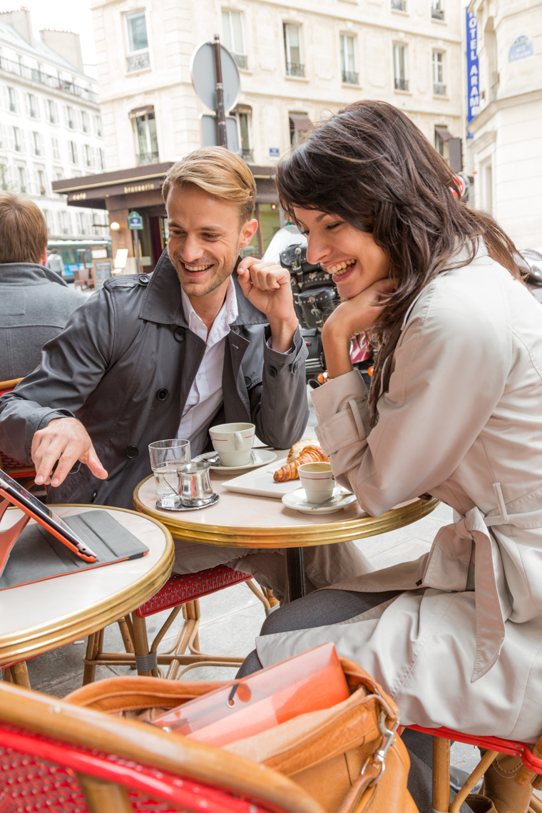 Couple at cafe looking at tablet computer