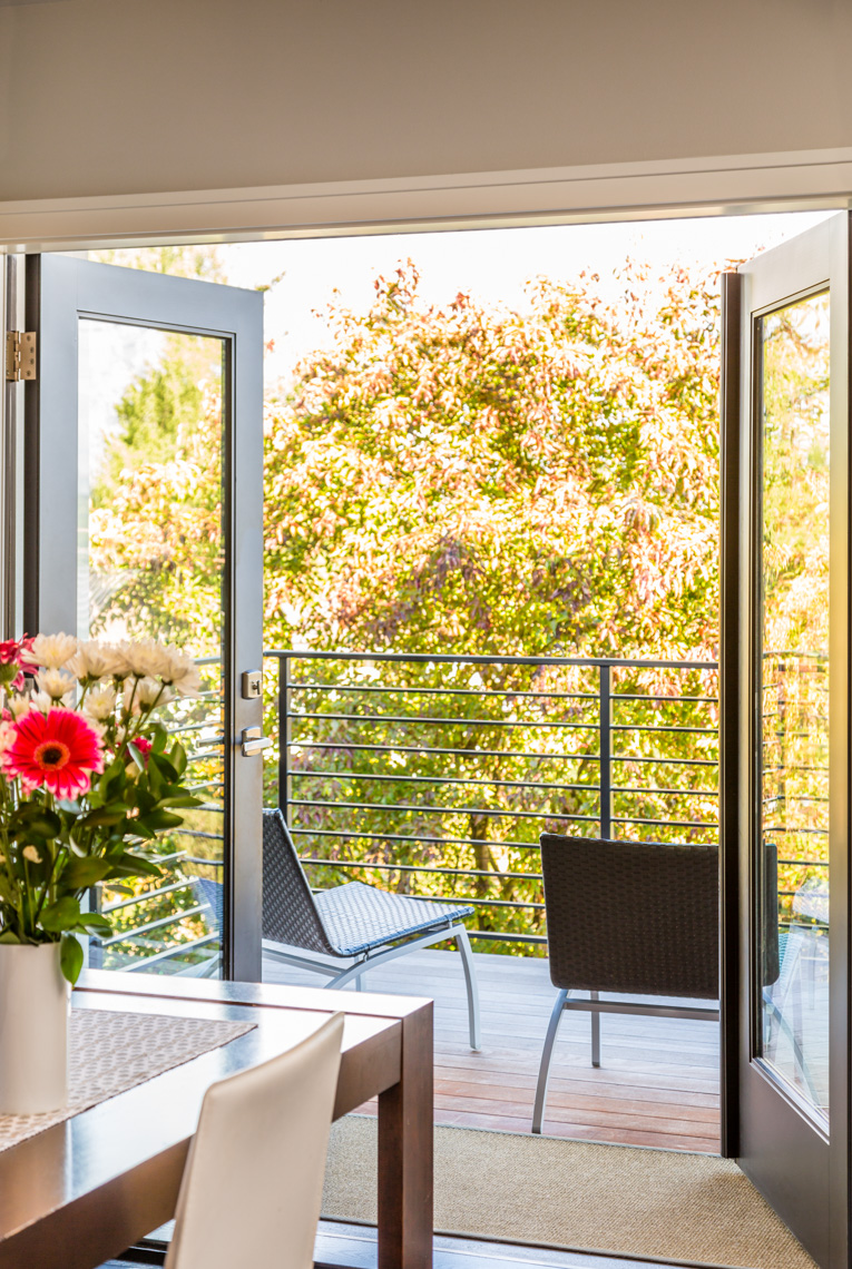 French doors windows opening to outdoor deck terrace in modern, contemporary, upscale home interior