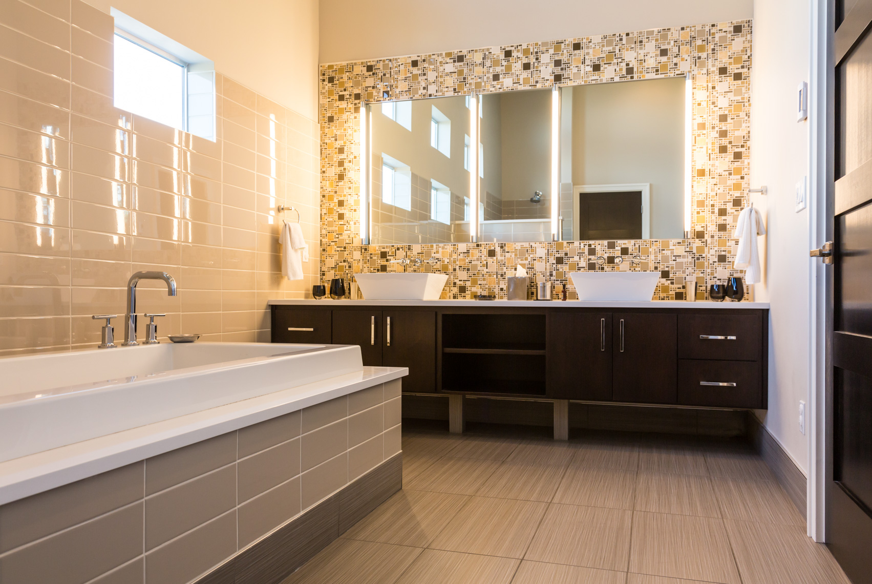 Contemporary upscale, modern home bathroom interior with tile walls and floors, vanity, mirrors, wood cabinets, acrylic soaking tub bathtub and high quality fixtures