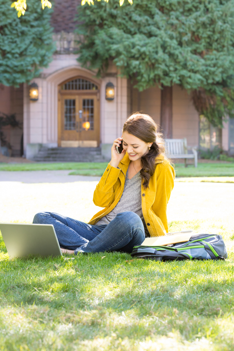 College student using laptop and cell phone on university campus