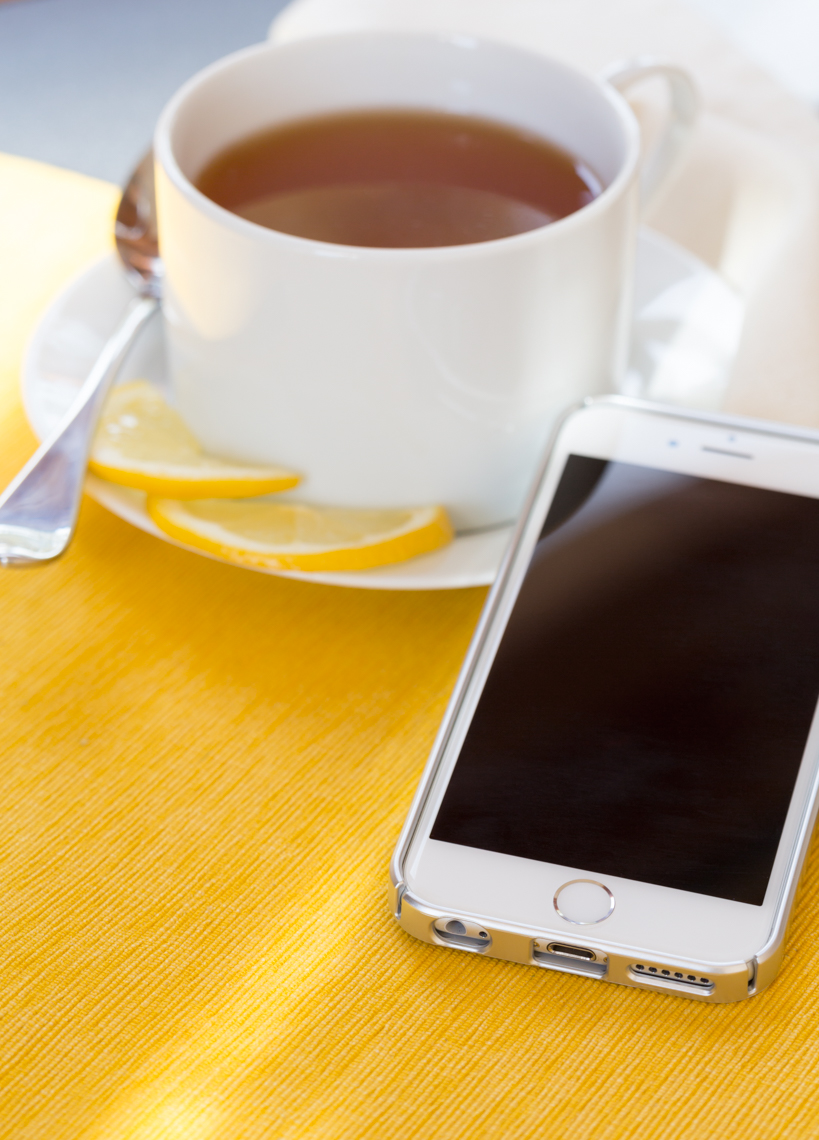 Cellular phone and cup of tea with lemon