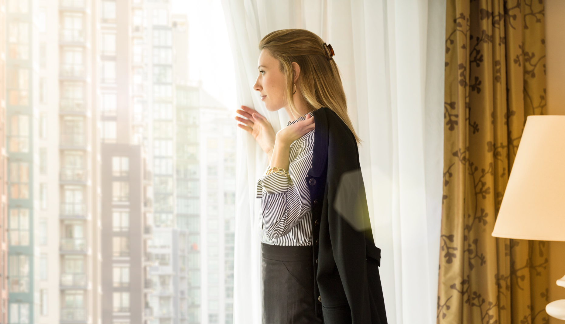 Woman businesswoman female business traveler looking out at city through hotel room window