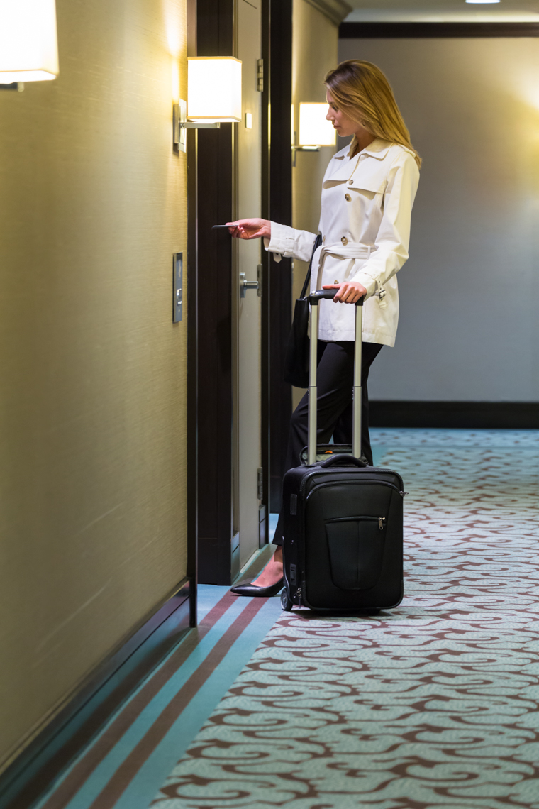Woman business traveler using keycard to open unlock hotel room door. Electronic security systems.