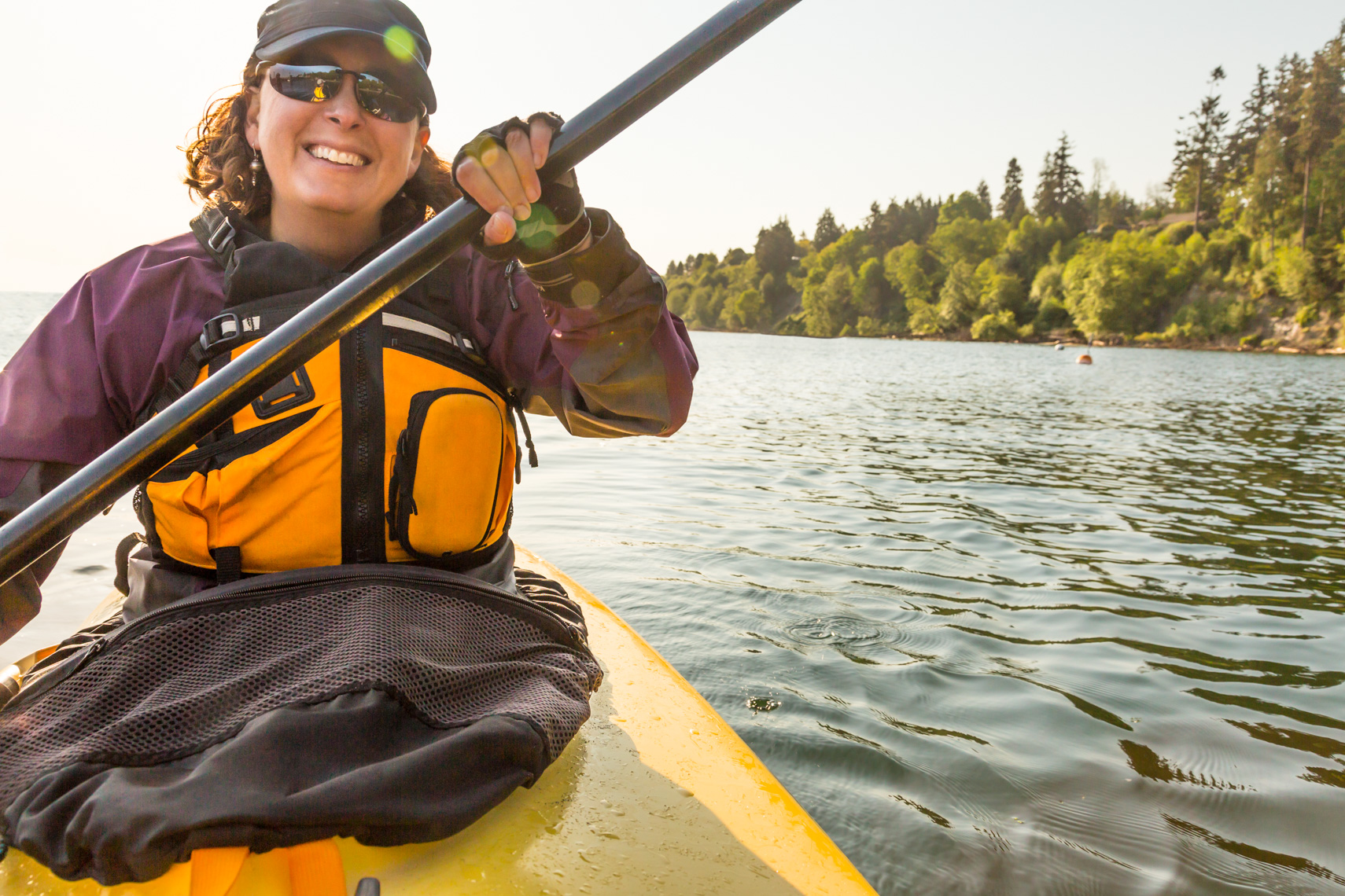 Happy, smiling, confident, healthy, middle aged woman wearing sunglasses and a life jacket sea kayaking. Active summer outdoor adventure water sports lifestyle.