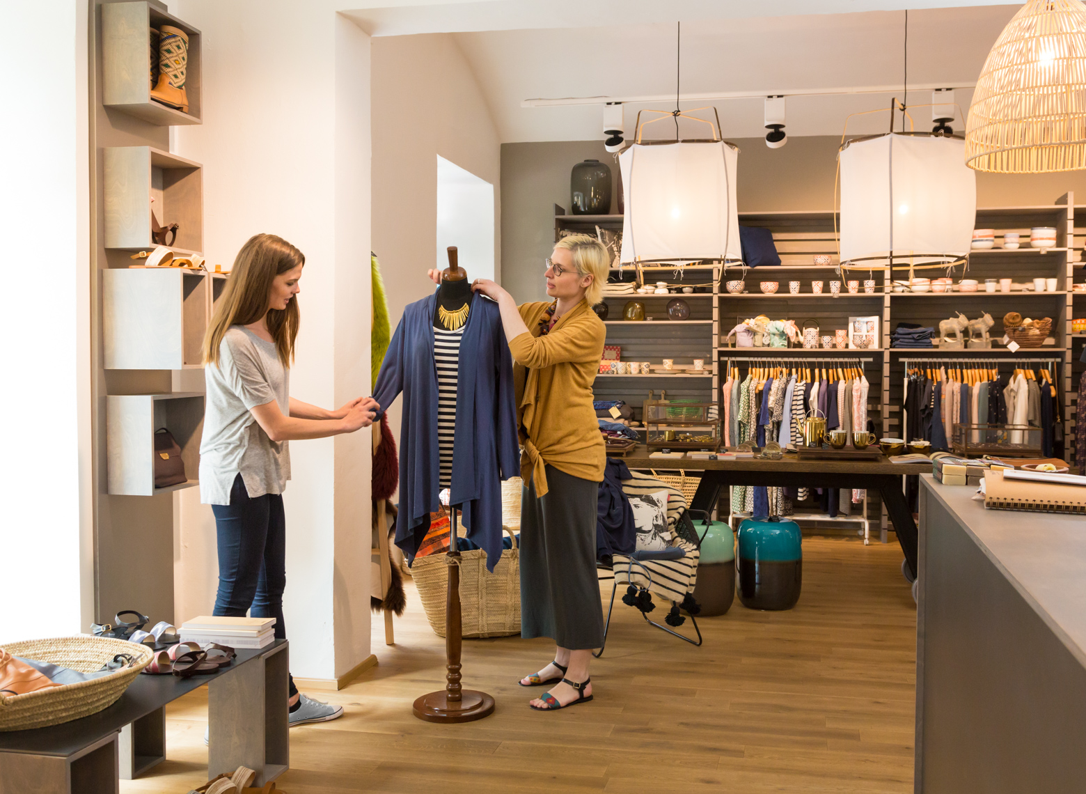 Women small business owner and employee working together arranging product displays in fashion clothing boutique shop store