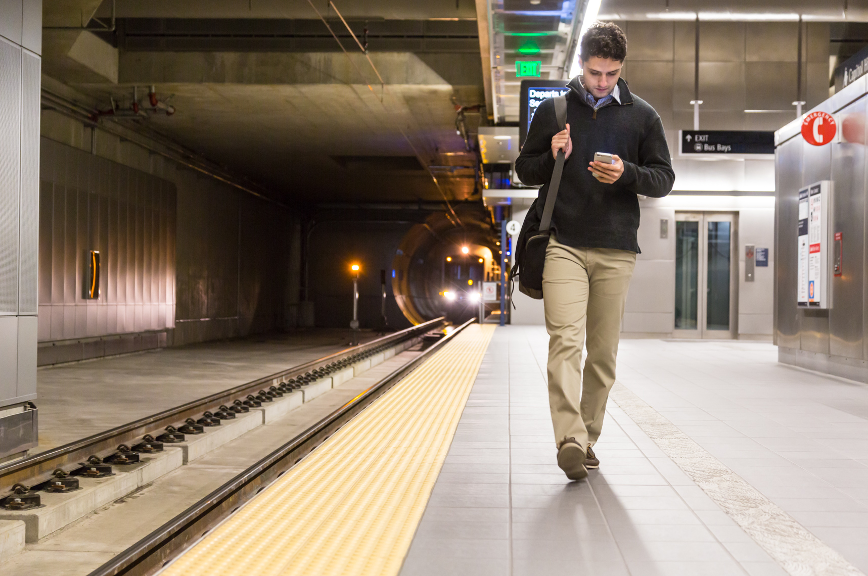 Young professional man with cell phone on subway platform. Mobile technology shoot.