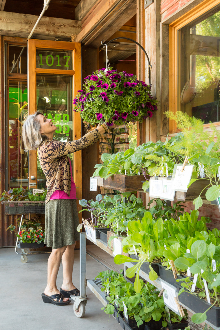 Happy smiling middle-aged woman customer shopping for flowers plants at a garden nursery shop store