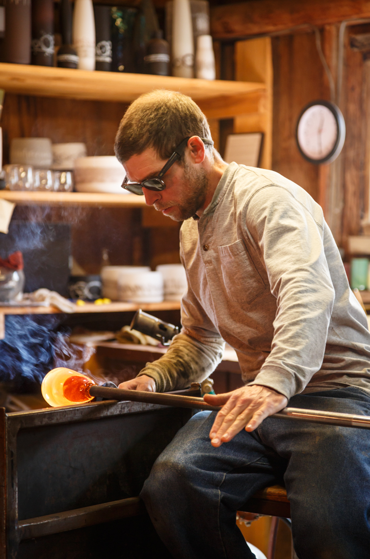 Glassblower artist craftsperson working with hot glass in his studio workshop