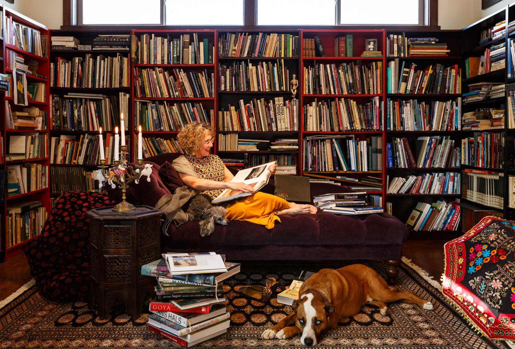 Happy, smiling, creative middle aged woman with her pet dogs relaxing reading a book in her unique home library interior