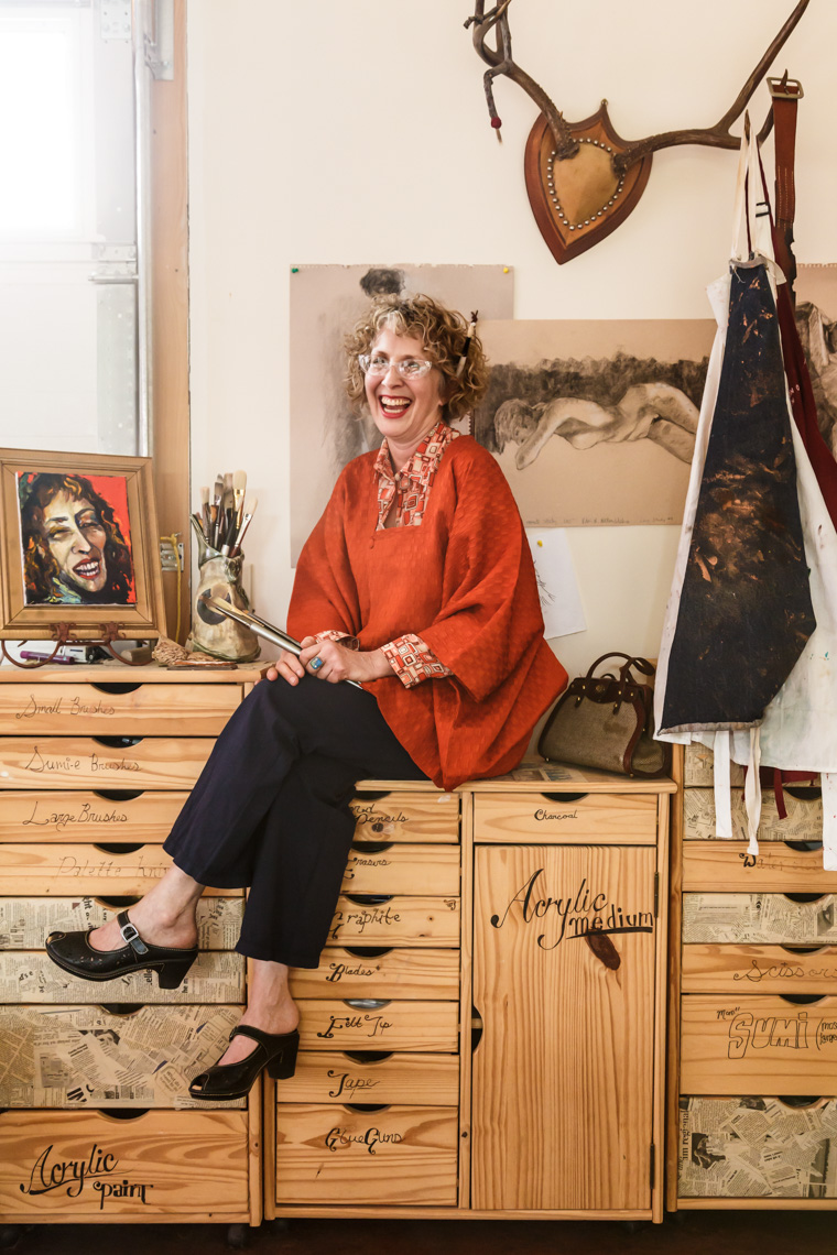 Happy, smiling, laughing, creative middle aged woman artist with art supplies in her studio