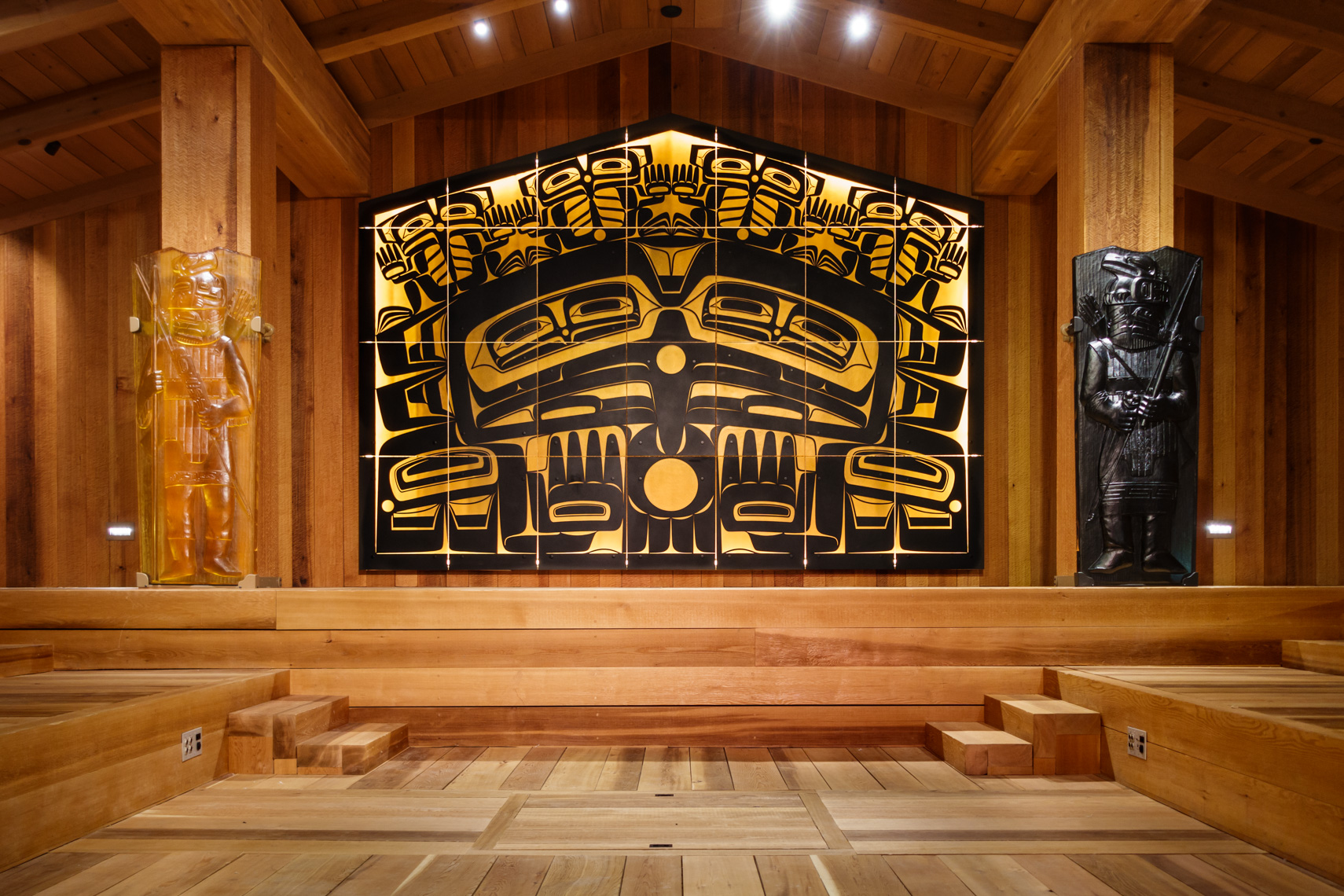 Interior of a traditional Northwest Coast Native American Indian tribal clan house, Juneau, Alaska. Glass house posts and a glass and metal screen by Tlingit artist Preston Singletary, in a typical formline art style, represent people, animals and supernatural beings.